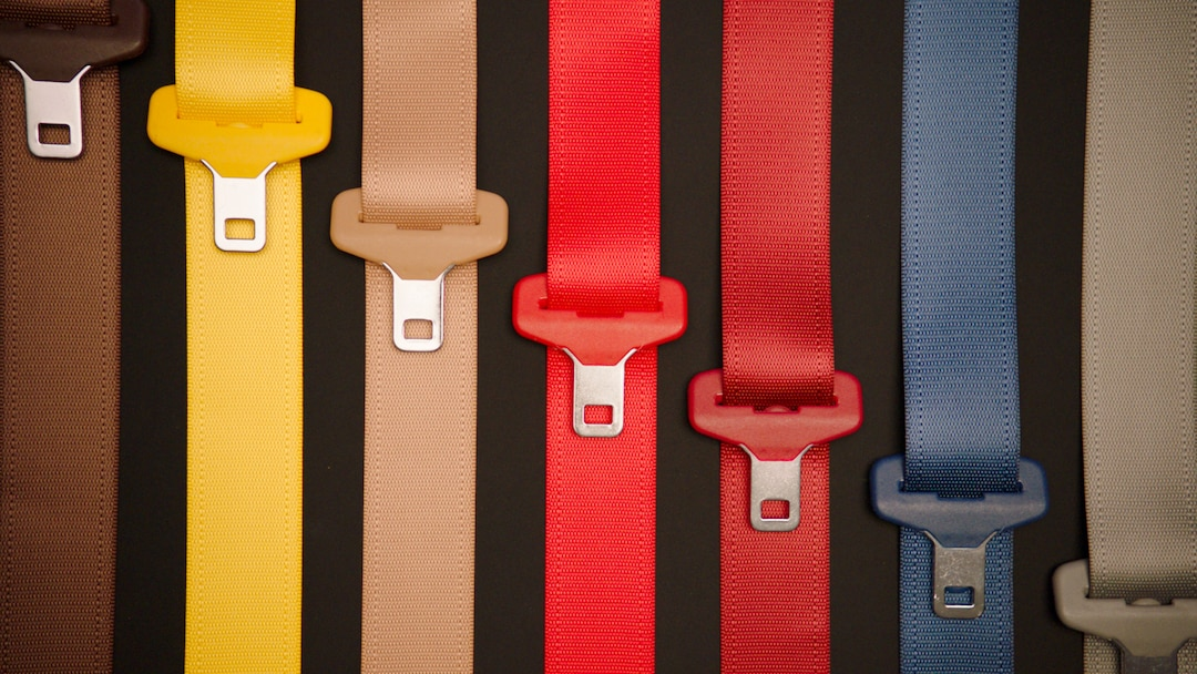Seatbelts in different colors from brown to gray through yellow, pink and red and blue