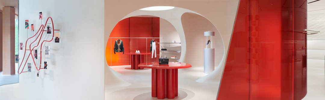Red table at the center of an oval space in the Maranello Store