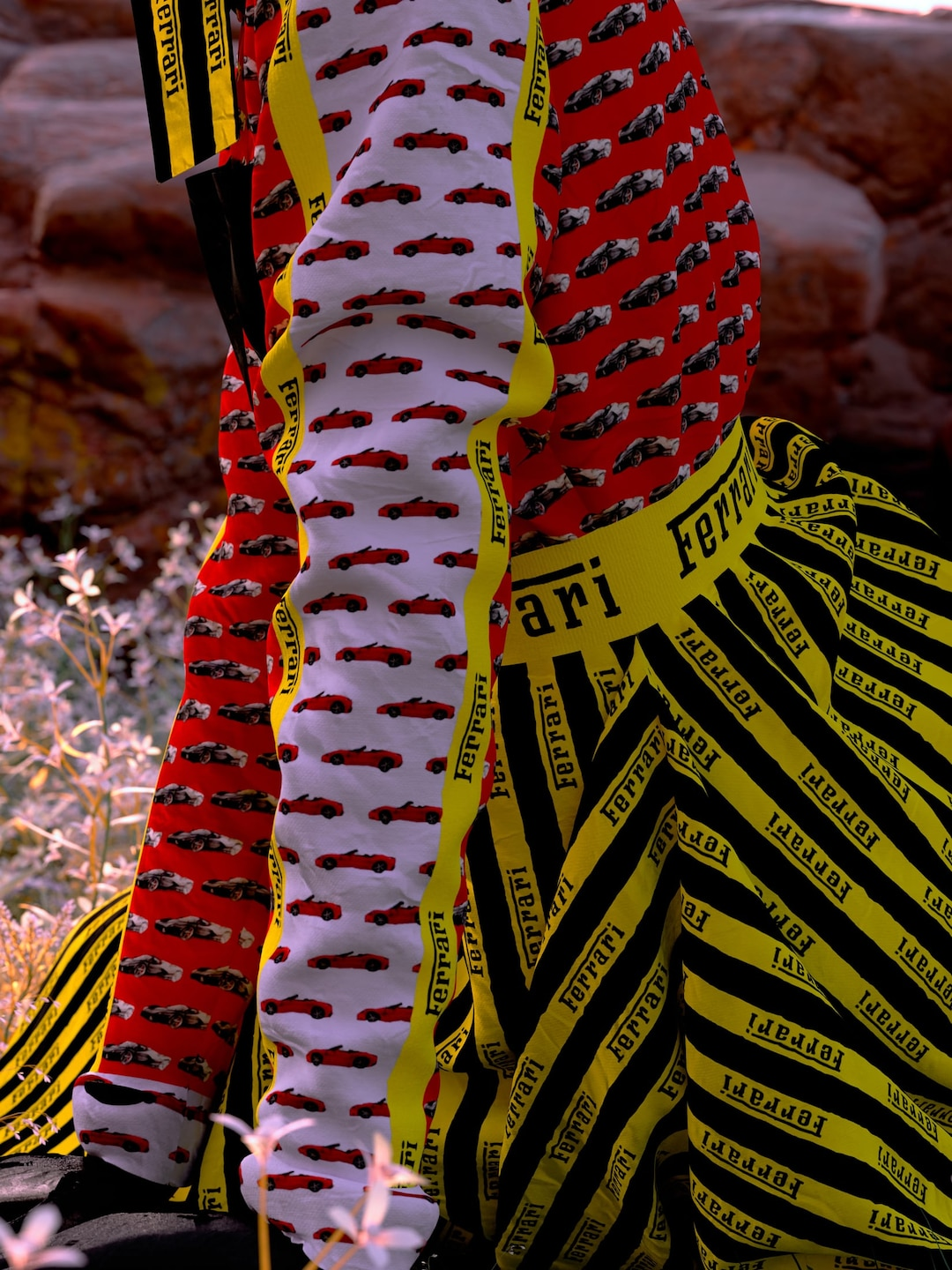 Red cars pattern in the white and red sleeve of a shirt worn with a yellow black-striped skirt