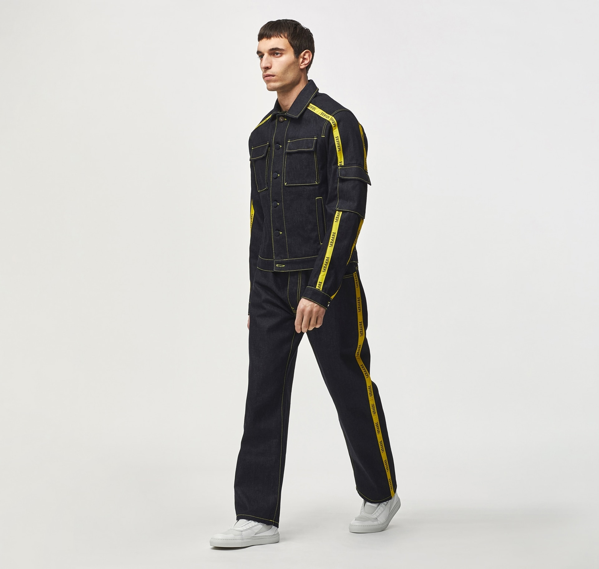 Model wearing a black denim suit with a yellow stripe and white sneakers