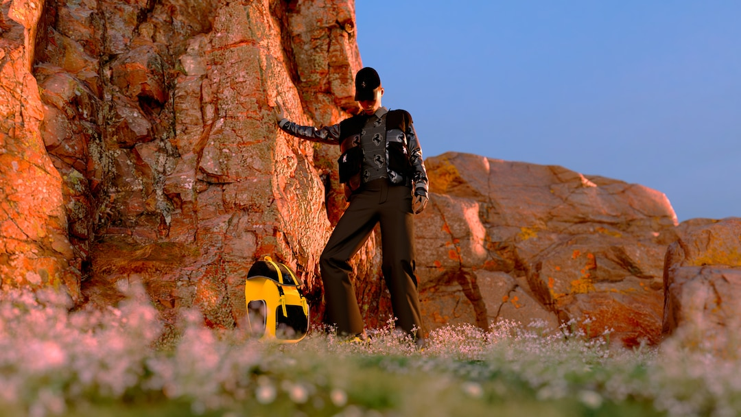 Model leaning on a rock wearing brown down jacket and brown pants in front of a yellow and black backpack