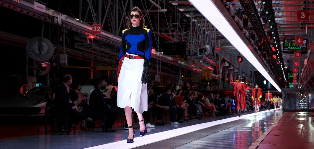 Model on the catwalk wearing black and blue sweater with yellow shoulders and white skirt with red belt