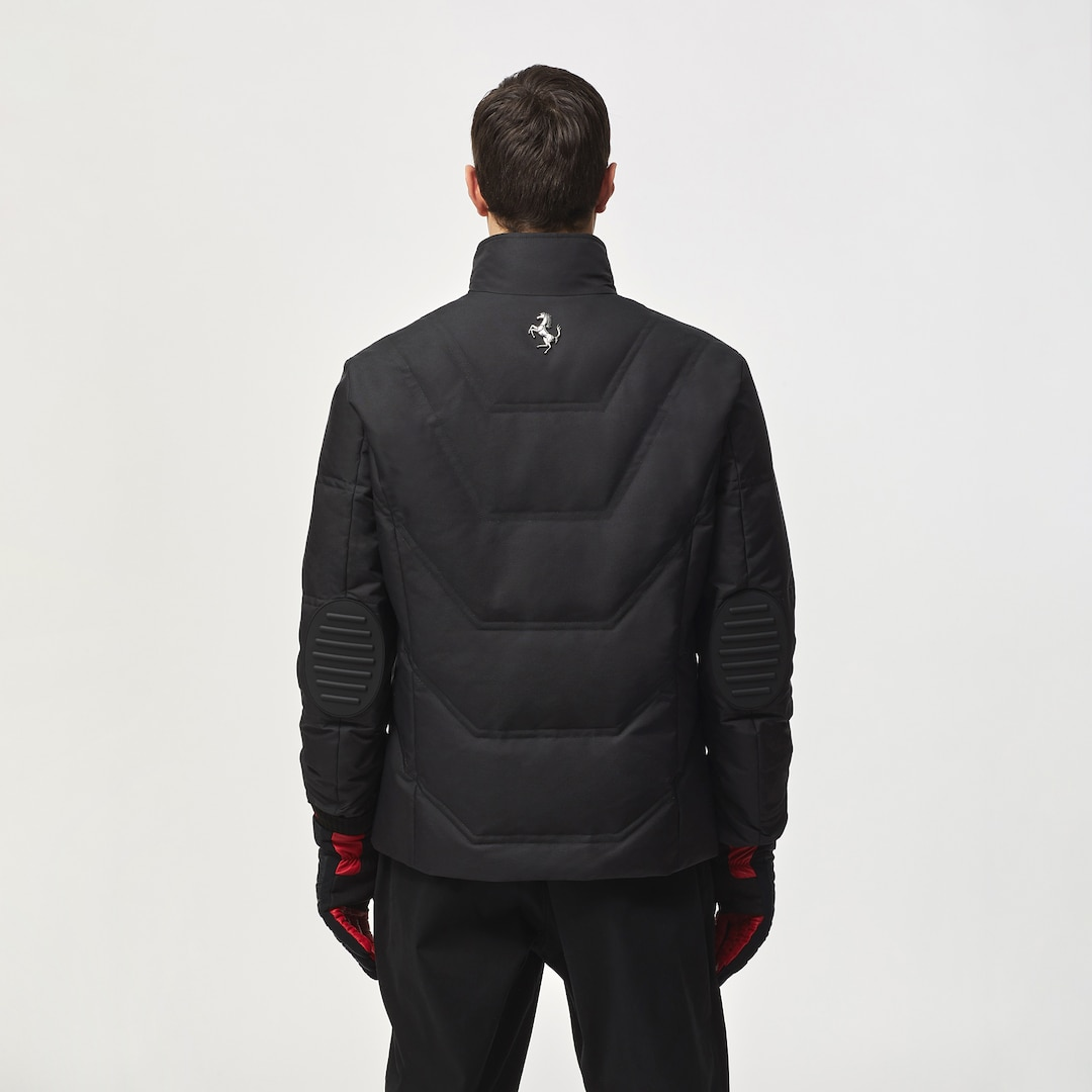 Back view of a model wearing a black jacket with elbow pads and silver Prancing Horse plated on neck
