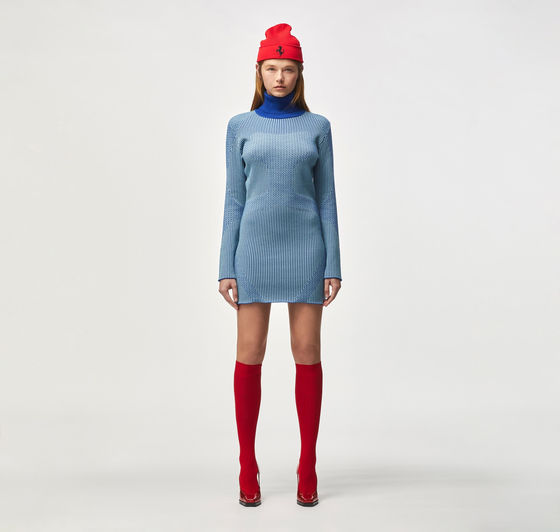 Model wearing light blue dress with blue collar, red cap and red boots