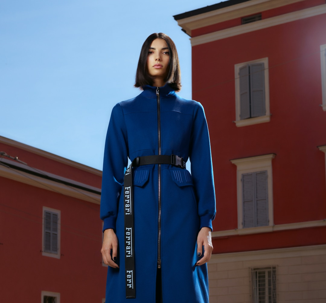 Model dressed in blue coat and black belt standing in front of red tinted buildings