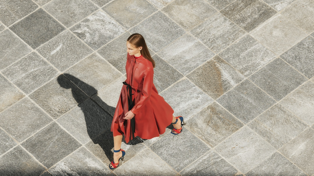Woman dressed in red leather dress and red pumps walking on stone tiles seen from above