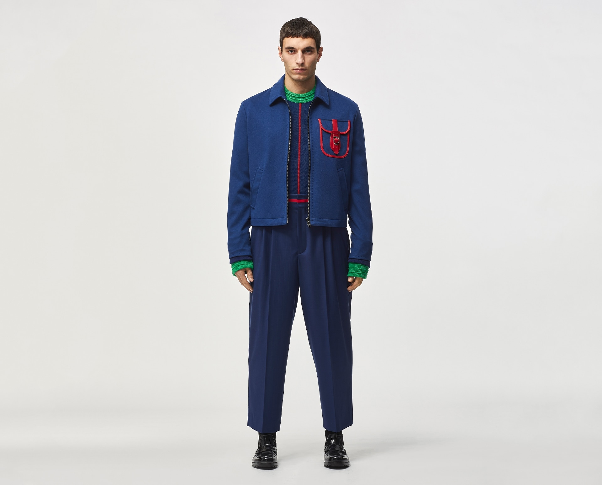 Model wearing blue sweatshirt with red and green details, blue trousers and black shoes